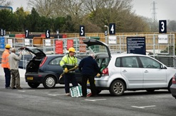 Residents and staff emptying a car at a Waste and Recycling centre