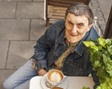 Elderly man drinking a cup of coffee on a bench